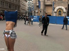 Girl is bound in the streets with her shirt over her head and her tits exposed.